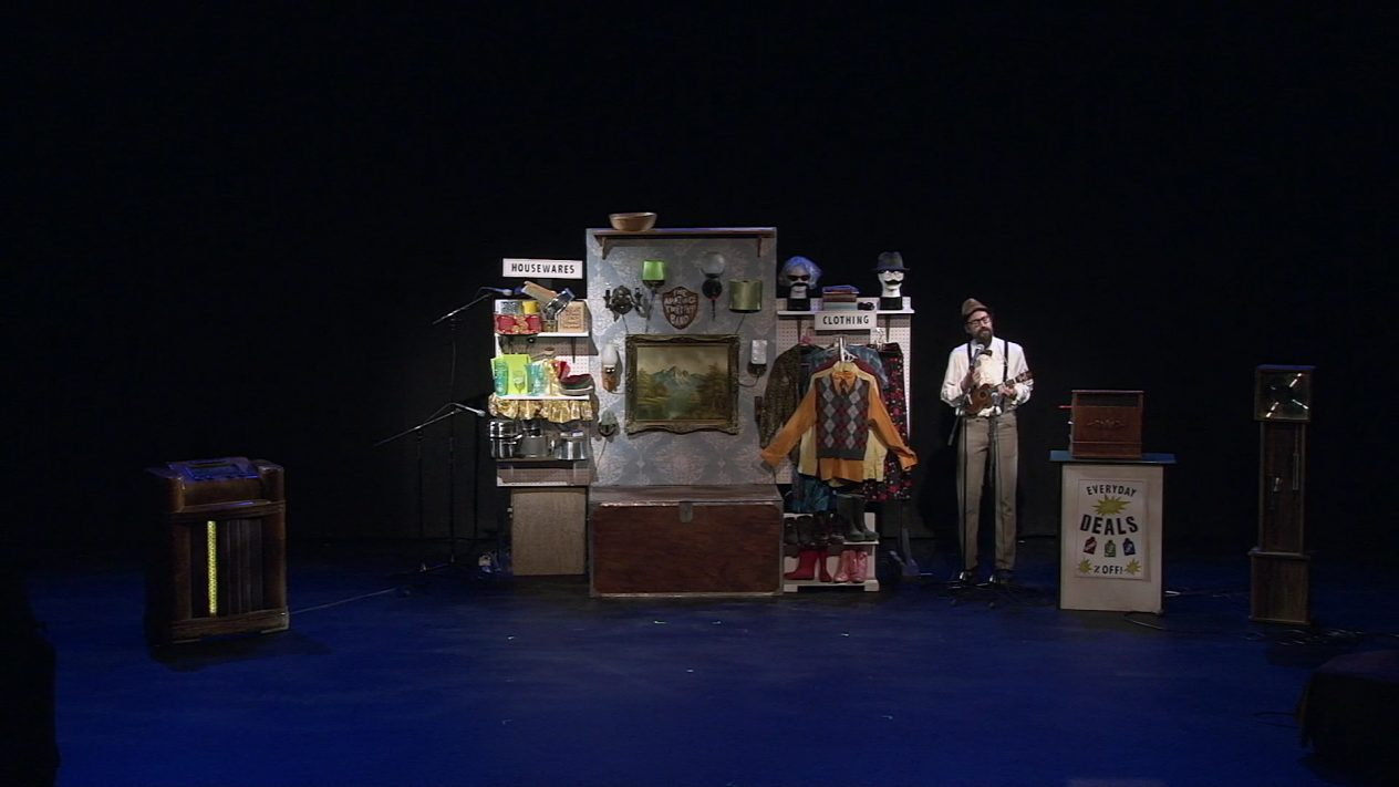 A man on stage standing beside a second of a thrift shop.